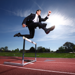 Businessman hurdling on a track