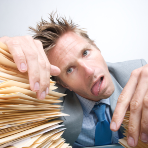 Exhausted businessman resting on a pile of paperwork with tongue hanging out from overwork