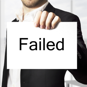 Businessman in a black suit holding up a white sign reading failed