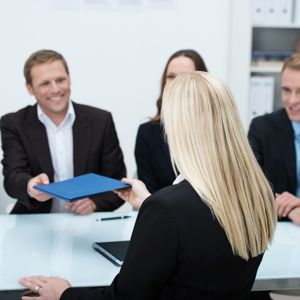 Blond female job applicant handing over her CV to a smiling businessman