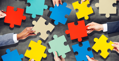Four business people's hands holding puzzle pieces